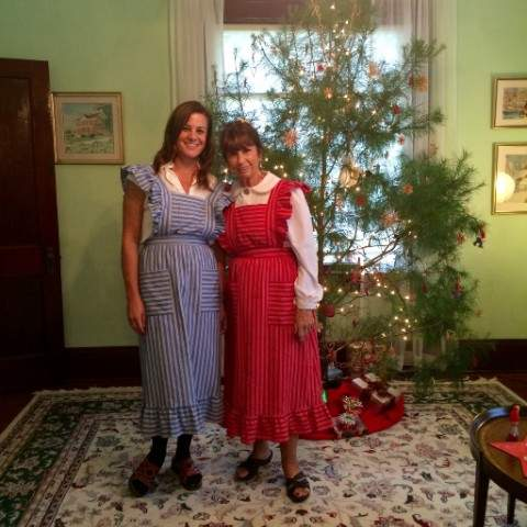 Two ladies dressed up in front of Christmas tree