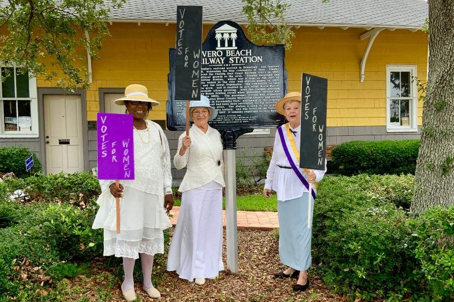 "Ladies holding ""Vote for Women"" signs in front of Vero Beach Railway Station historical sign"