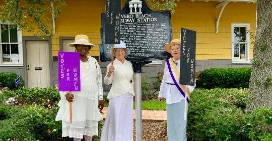 "Ladies holding ""Vote for Women"" signs in front of ""Vero Beach Railway Station"" historical sign"